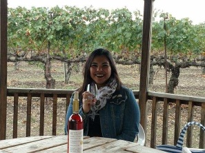 Moni holding up a wine glass, at a vineyard in Livermore.